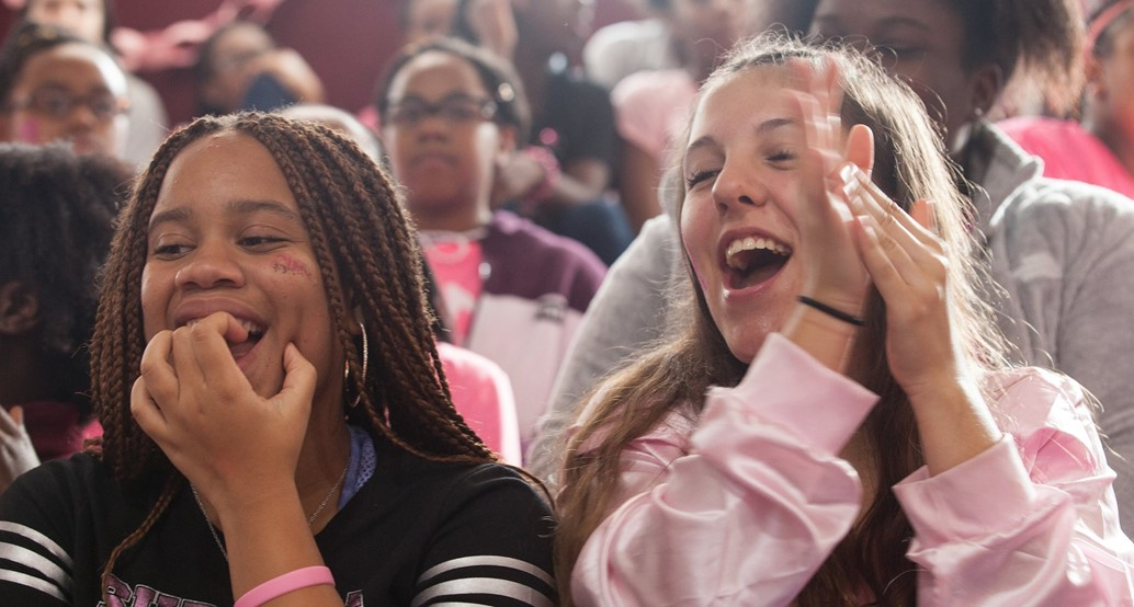 two students cheering in stands