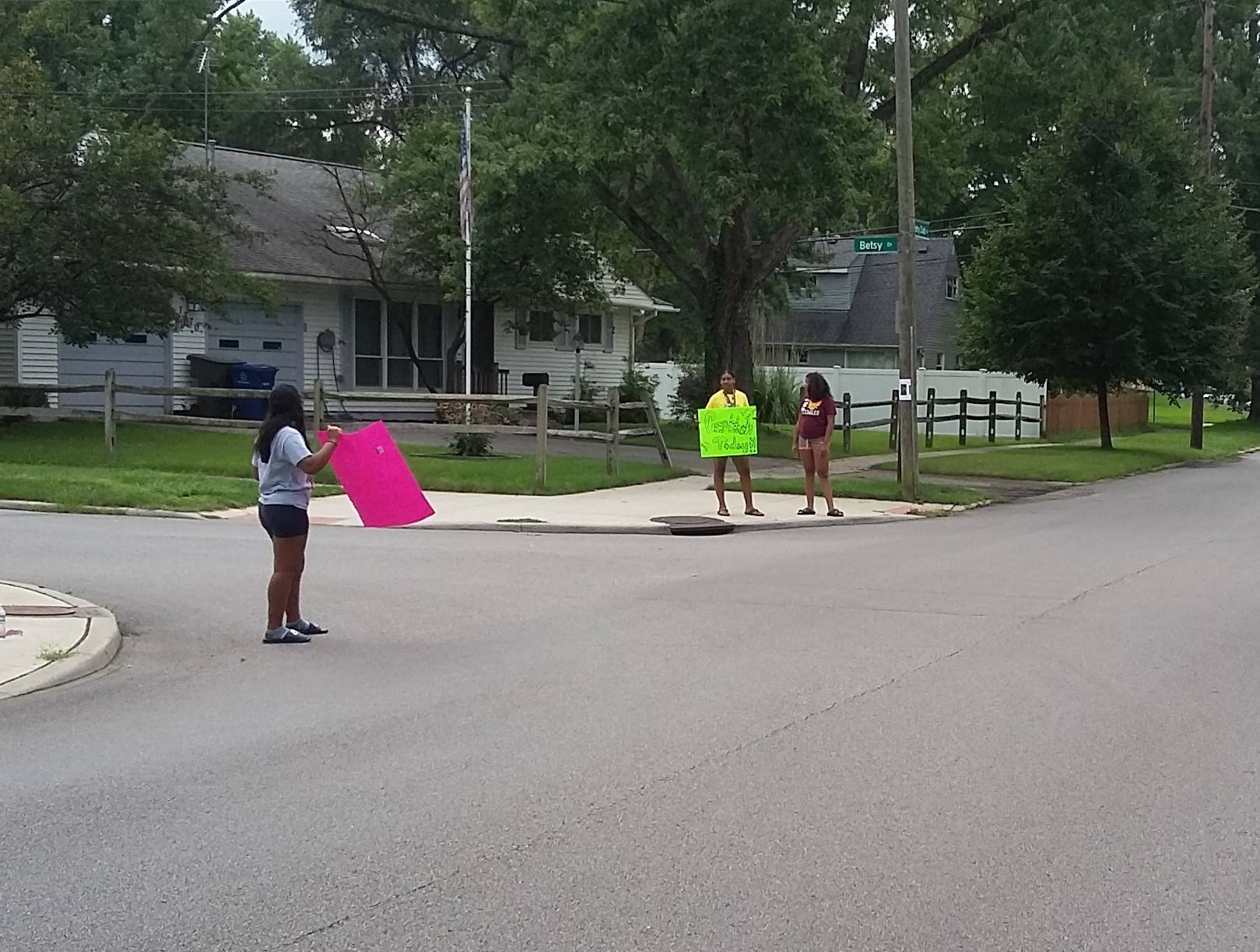 Students on sidewalk with car  wash signs