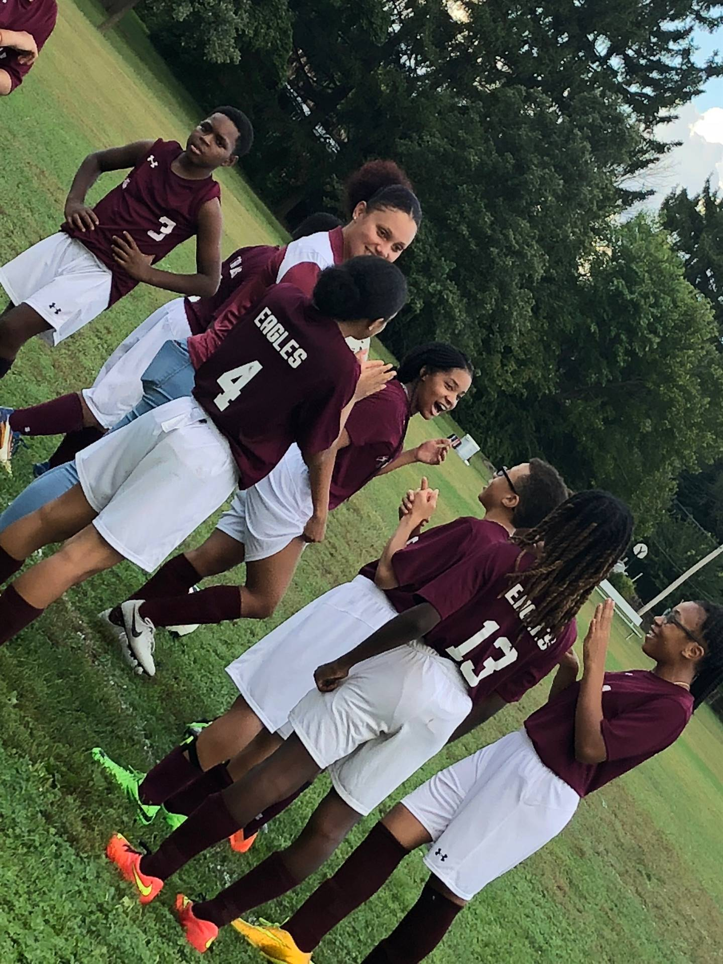 students in soccer uniforms in huddle