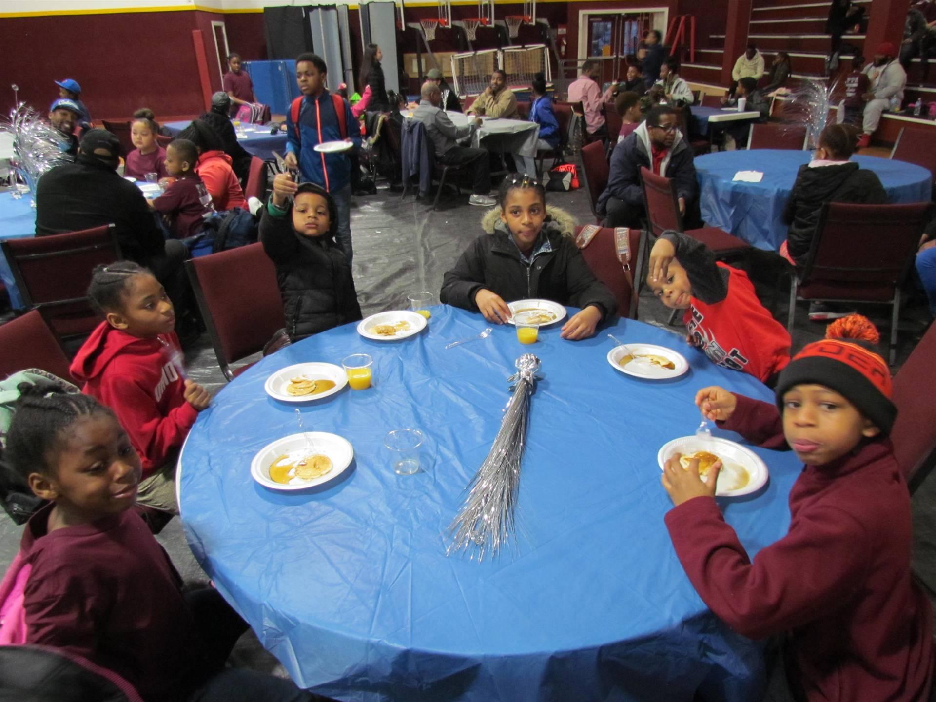 6 kids at table eating pancakes