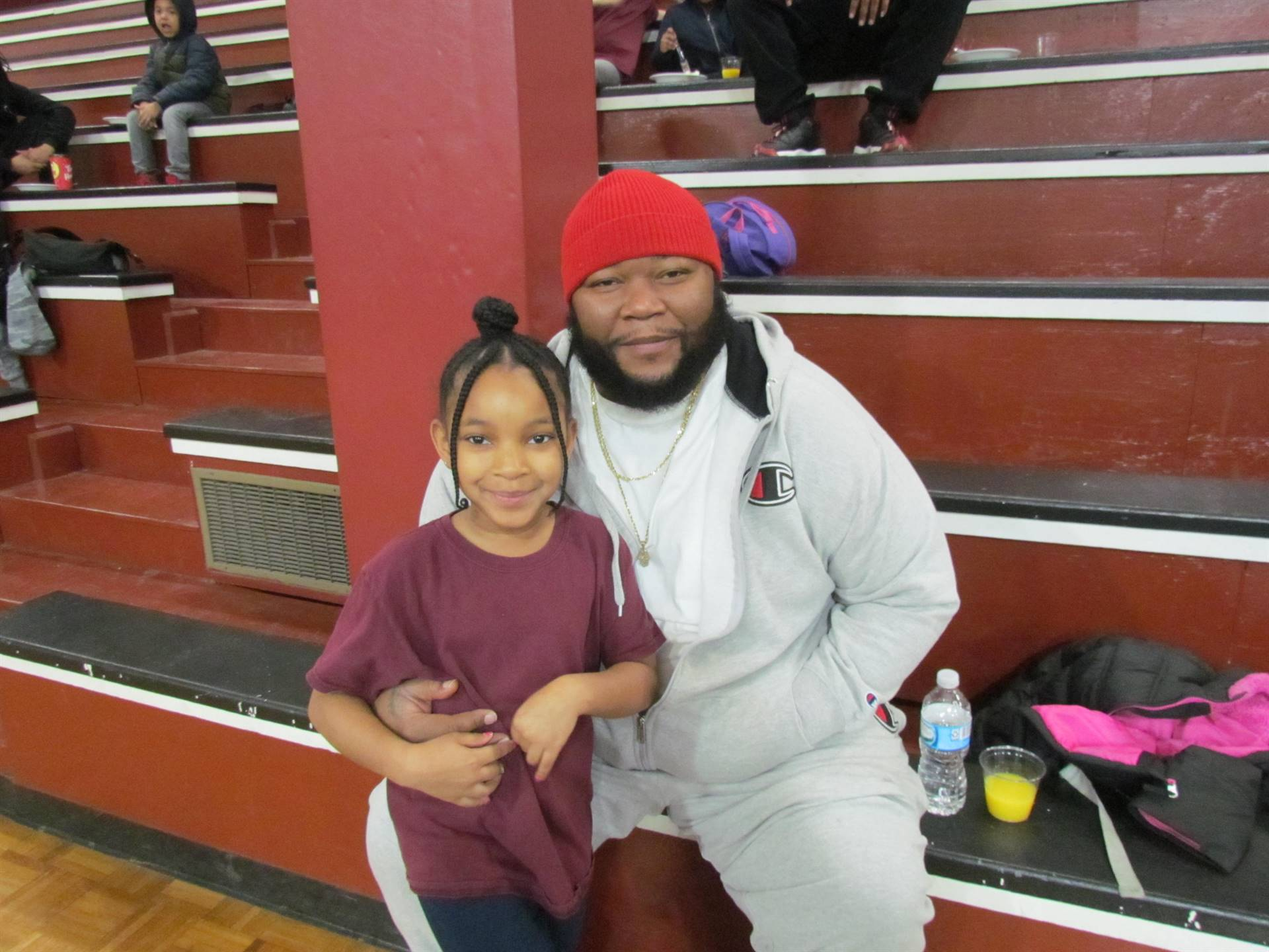 dad posing with daughter on bleachers