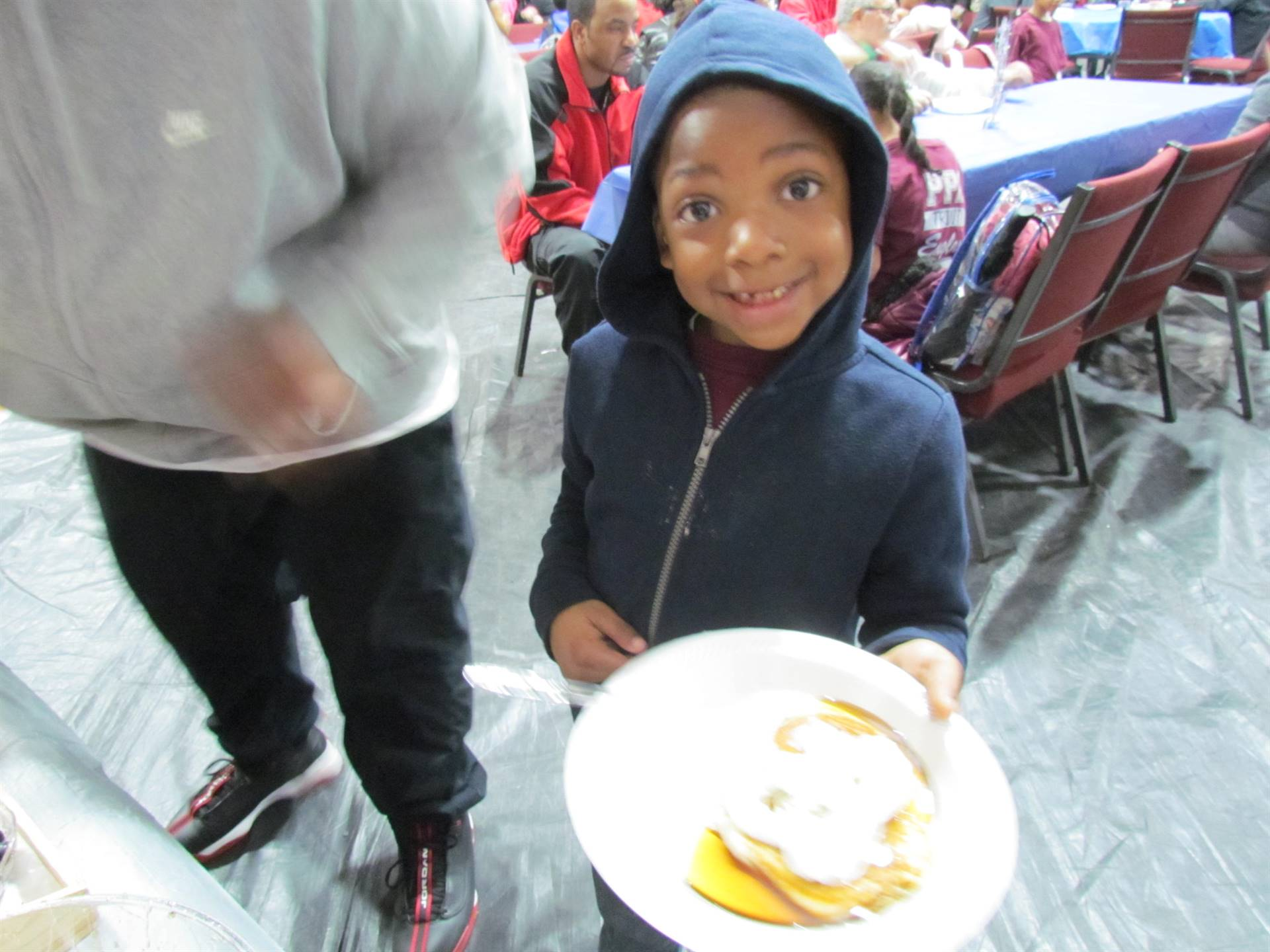 boy holding pancake on plate