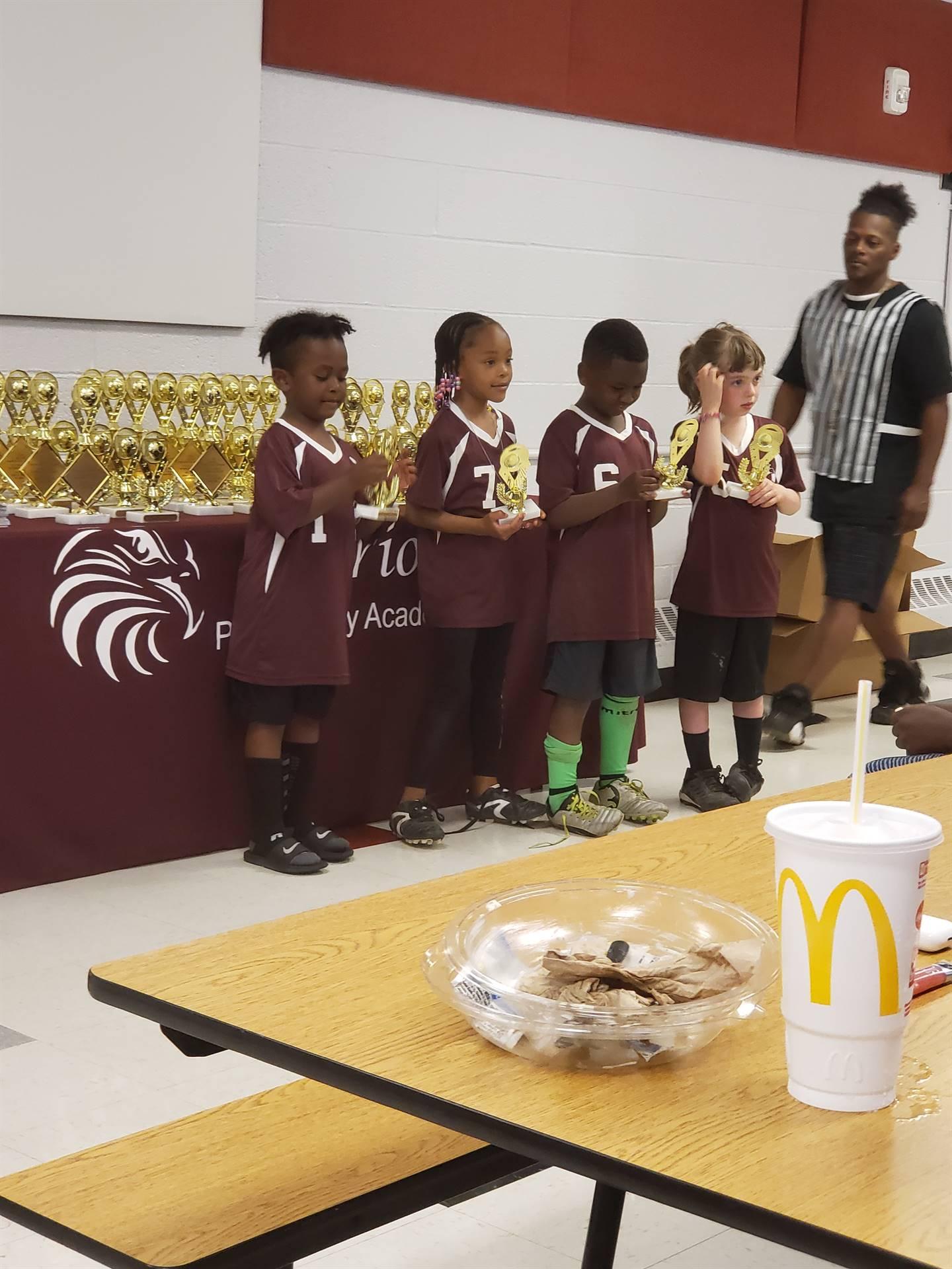 kids getting soccer trophies