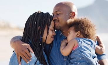 man kissing woman's forehead while holding a toddler