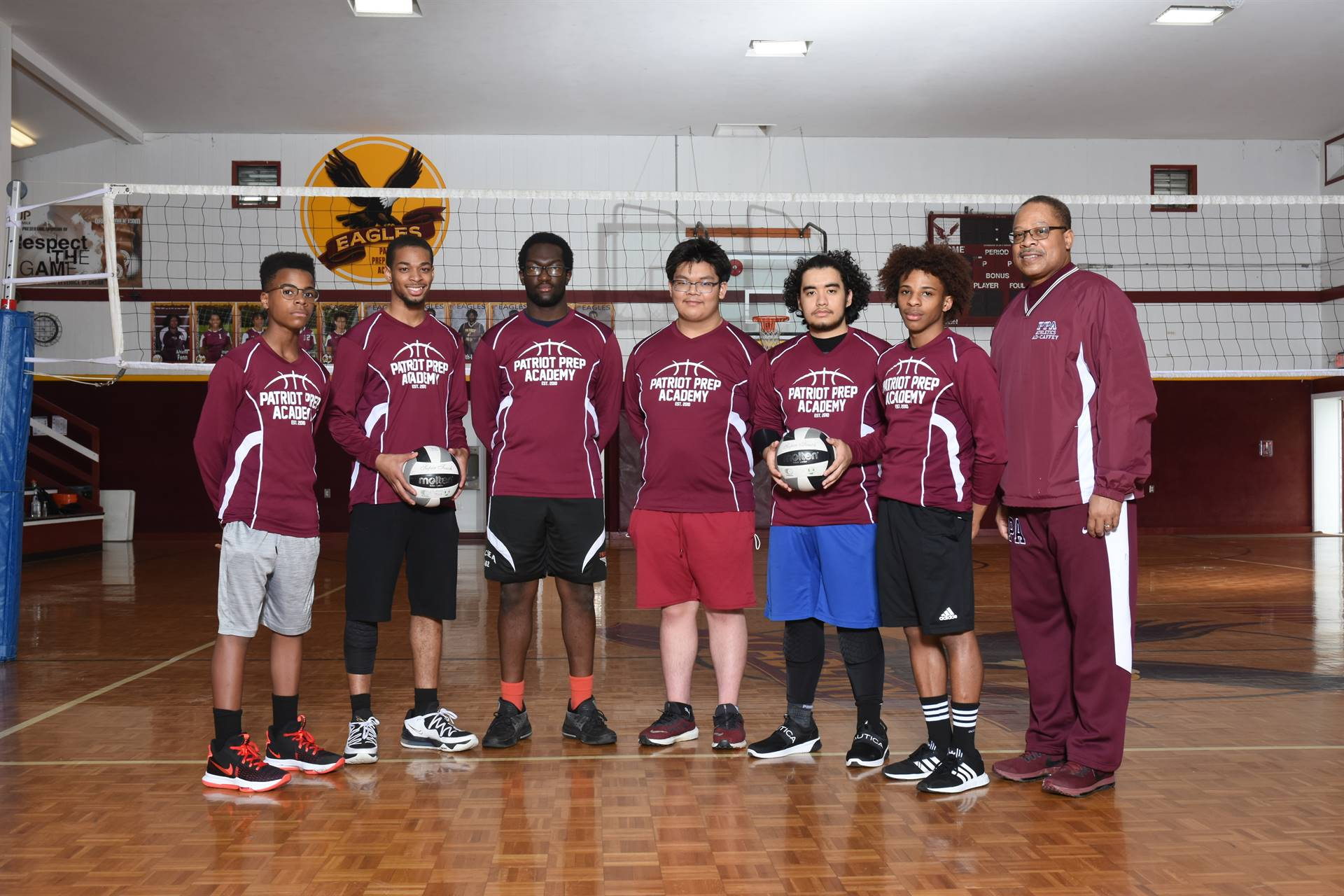 6 students in volleyball uniforms and coach in gymnasium