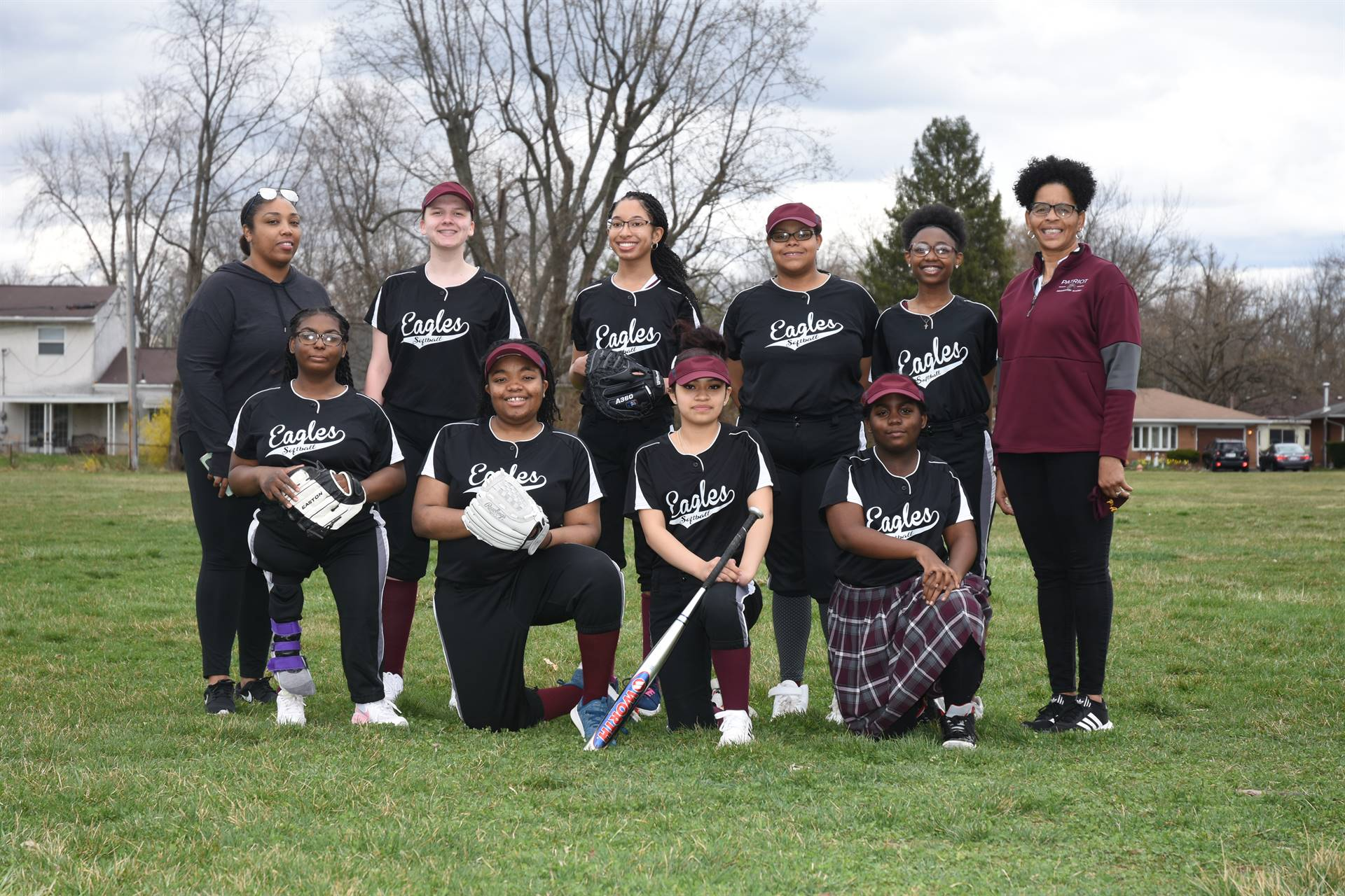 14 students in softball uniforms and coach outside