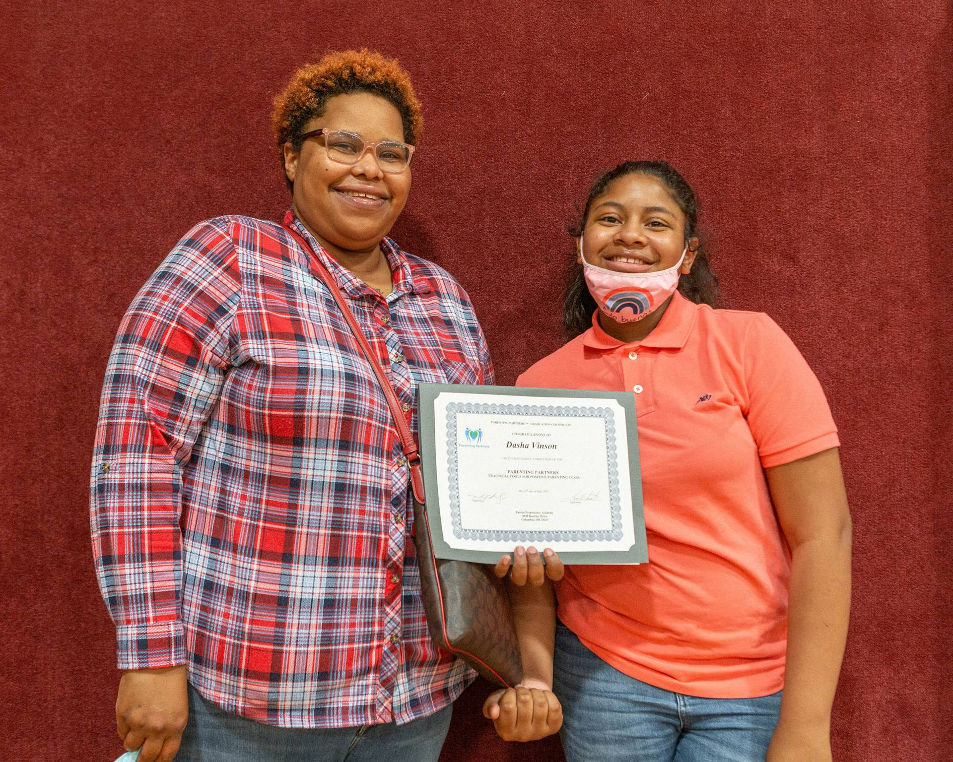 mother and daughter holding certificate