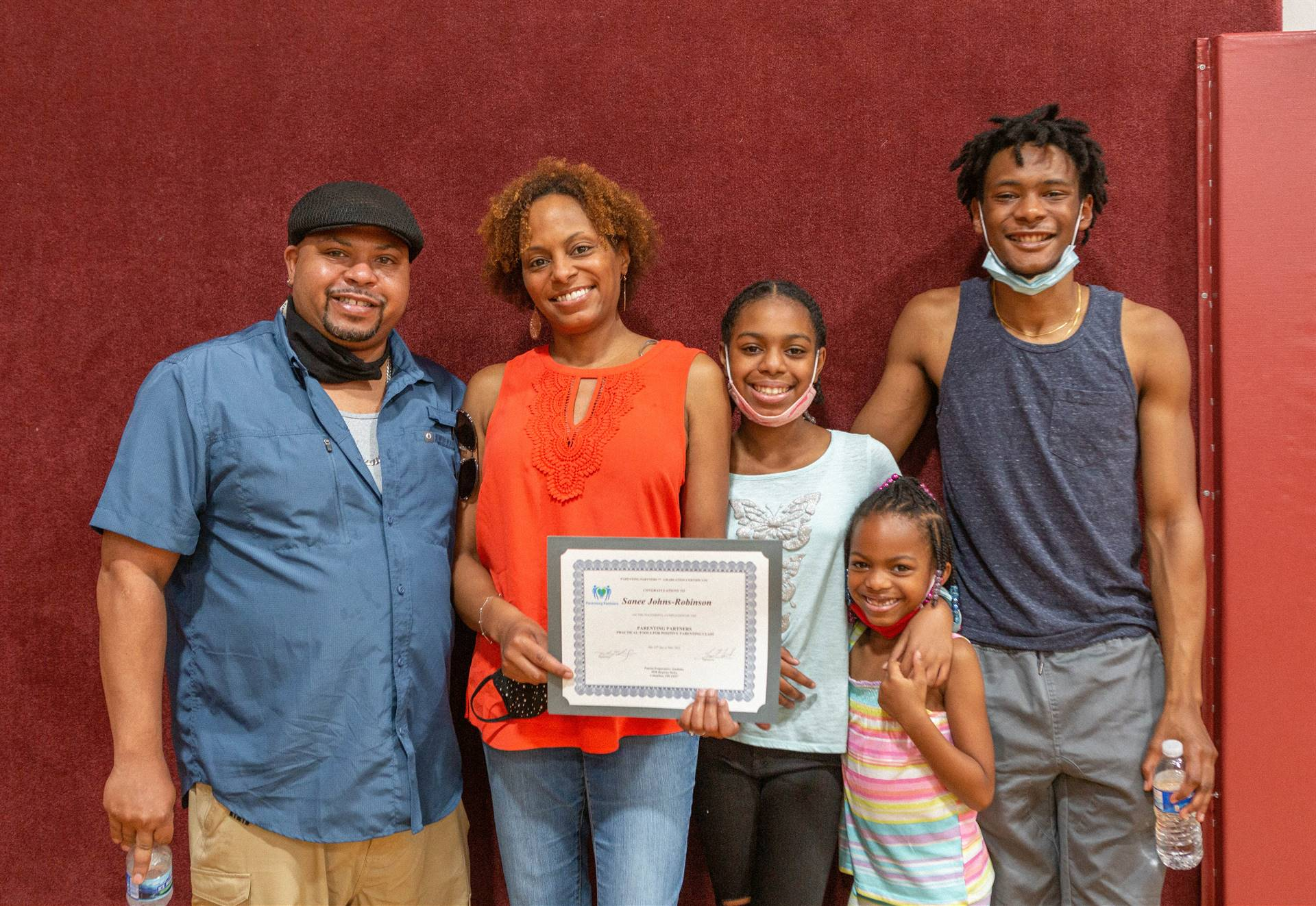 mother, father, son, and 2 daughters with certificate
