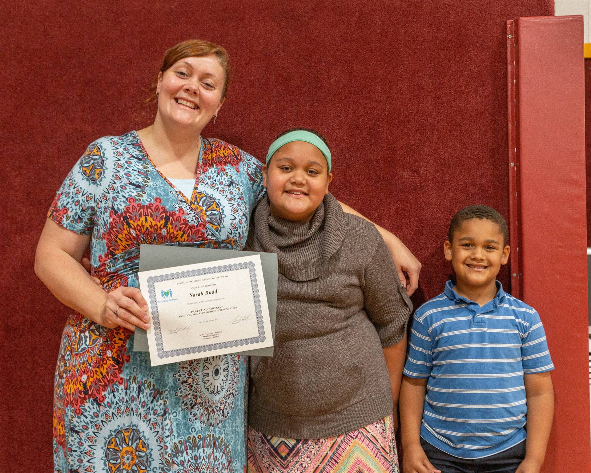 mother, son, and daughter holding certificate